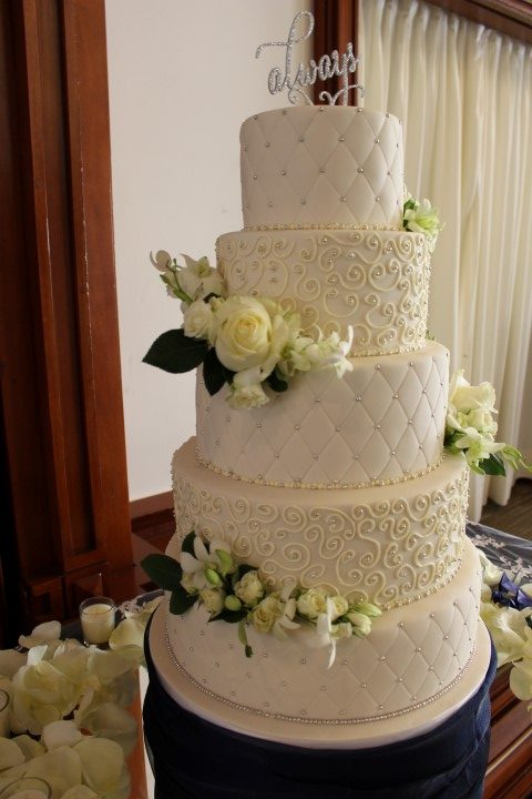 Diamond pattern white wedding cake with fresh flowers
